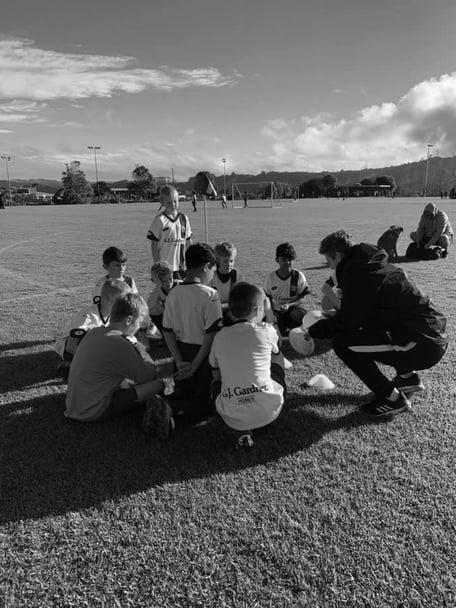 Kids and coach on the grass at Huapai Domain